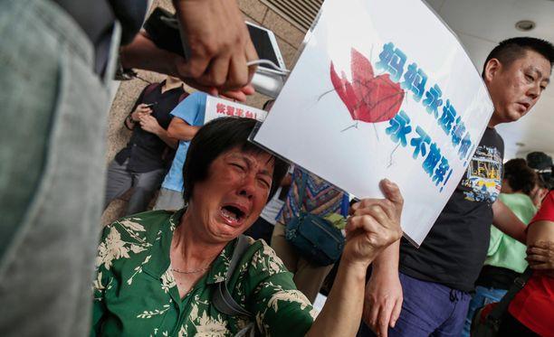 Nainen itki tänään Malaysia Airlinesin toimiston ulkopuolella Pekingissä Kiinassa. MH370-koneen matkustajien läheiset ovat olleet pettyneitä tutkintoihin.