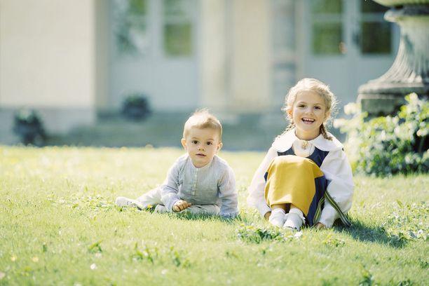 Ulkona otetussa kuvassa sisarukset istuskelevat nurmikolla.