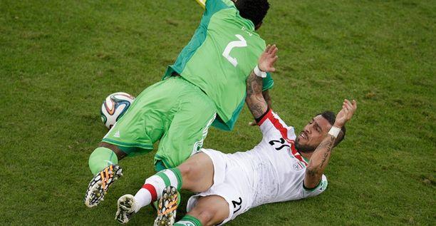 Nigerian Joseph Yobo kellahtaa Iranin Ashkan Dejagahin päälle.