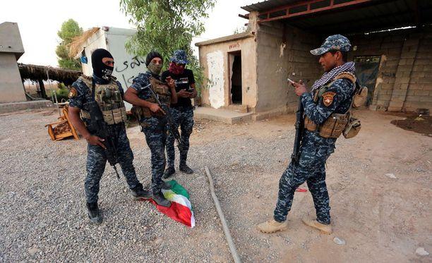 Irakilaispoliisit kuvattiin tallomassa Kurdistanin lippua valtauksen jälkeen.