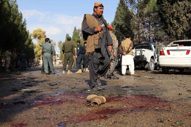Afganistanin turvallisuusjoukot tutkivat itsemurhapommituksen paikkaa Lashkar Gahissa lauantaina. Iskun kohteena oli armeijan auto.