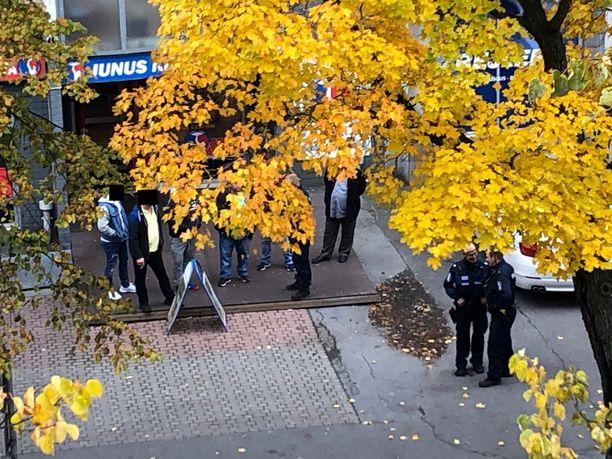 Poliisi puhutti ja valokuvasi useita ihmisiä joukkotappelupaikalla.