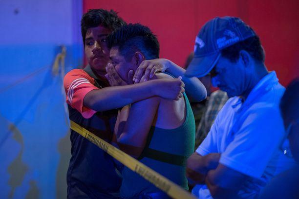 Uhrien omaiset odottivat uutisia baarin edessä.