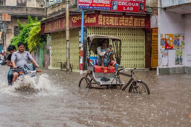 Ihmiset pyrkivät jatkamaan arkielämäänsä tulvien keskellä Intian Varanasissa 11.8.2019.