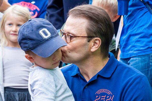 Prinssi Daniel suukotti poikaansa liikuntatapahtuman yleisössä.