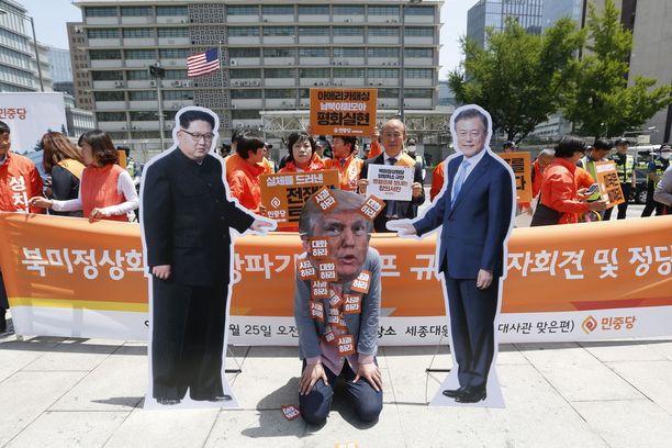 Trumpia esittävä mielenosoittaja polvistui Koreoiden johtajia esittäneiden pahvihahmojen väliin USA:n suurlähetystön edustalla Soulissa perjantaina.
