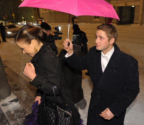 Laura Lepistön seuralainen suojasi neidon kampausta lumisateelta pinkillä sateenvarjolla.