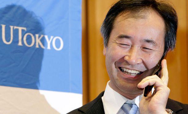 Japanilainen Takaaki Kajita keskustelee puhelimessa Japanin pääministerin kanssa kuultuaan saamastaan Nobel-palkinnosta.