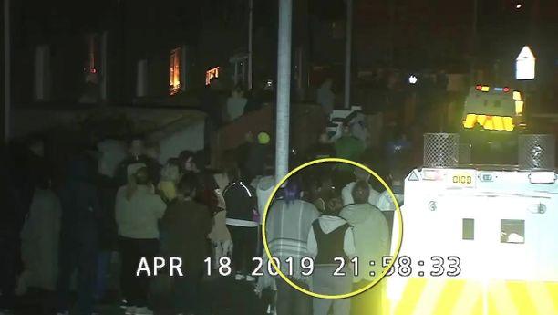 Pohjois-Irlannin poliisin julkaisemasta videosta otetussa kuvassa näkyy miten toimittaja Lyra McKee (ympyröity) seisoo poliisiauton vieressä.