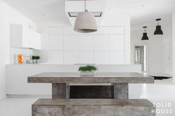 Simppeli betoninen ruokaryhmä kruunaa tämän valkoisen keittiön.