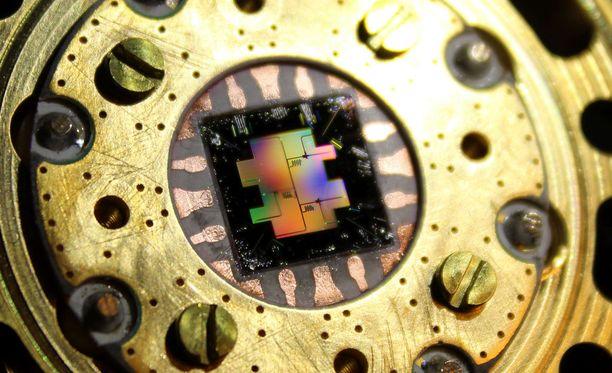 Valokuva senttimetrin kokoisesta piisirusta, jonka päälle on rakennettu kolme erillistäsuprajohtavaa kvanttibittiä.