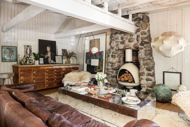 Raskaita, suuria huonekaluja ja pehmeitä tekstiilejä. Massiivinen, peilipintainen sohvapöytä keventää runsasta sisustusta.