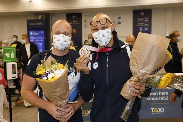 Eetu Karvonen ja Matti Mattsson poseerasivat pronssimitalin kanssa Helsinki-Vantaan lentokentällä.