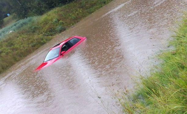 Punainen auto jäi jumiin keskelle tulvivaa alikulkua.