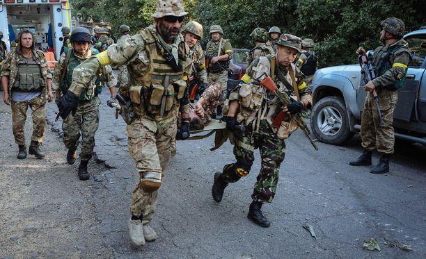 Ukrainalaissotilaat kantavat haavoittunutta Ilovaiskin taisteluissa elokuussa 2014.