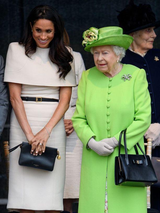 Jännittynyt Meghan ottaa asentoonsa mallia kuningattaresta. Judi Jamesin tulkinnan mukaan Meghanin tiukasti vartaloa myöten pitämät käsivarret ja tiukka ote laukusta kertovat pelokkuudesta. Kuningatar seisoo tyynenä. Meghanin olemuksesta paistaa vasta-alkajan yritys ottaa oppia katsomalla.