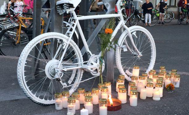 Ihmiset sytyttivät kynttilöitä onnettomuuspaikan viereen tuodun valkoisen polkupyörän luona.