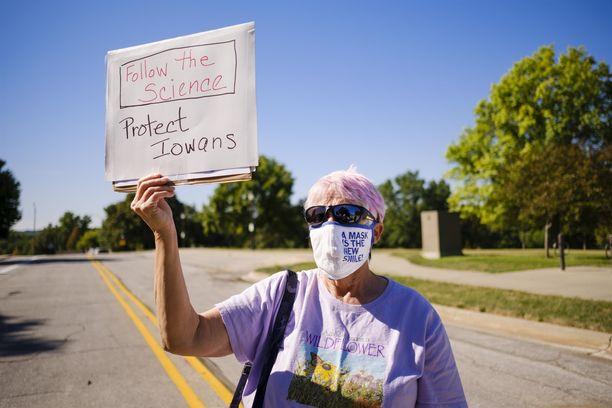 Kasvomaskit puhuttavat ympäri maailman. Kuvassa maskisuositusta vaativa nainen Iowassa, Yhdysvalloissa.