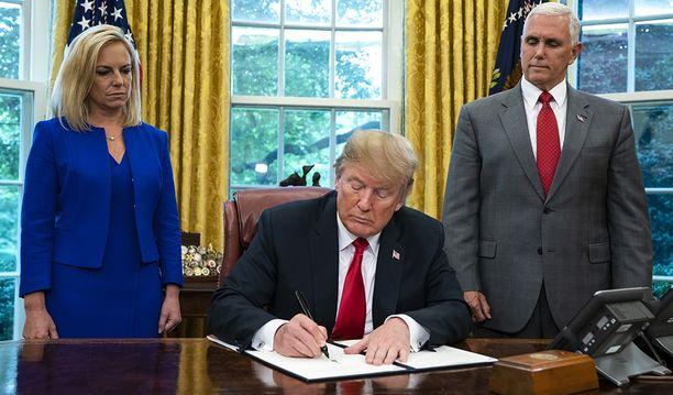 Trump allekirjoitti määräyksen keskiviikkona Valkoisessa talossa. Mukana olivat varapresidentti Mike Pence ja kotimaisen turvallisuuden ministeri Kirstjen Nielsen.