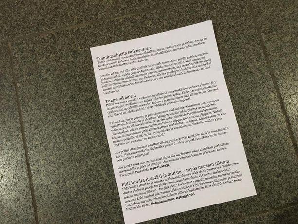 Vastamielenosoittajat jakoivat osallistujille toimintaohjeita paperilla.