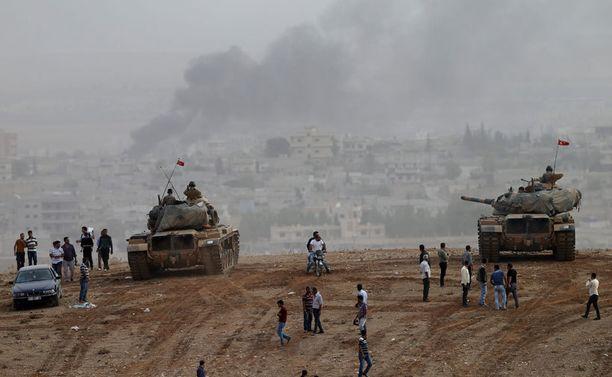 Turkin puolelle paenneet ihmiset seurasivat Turkin panssarivaunujen vierellä rajan toisella puolella käytäviä taisteluja lauantaina.