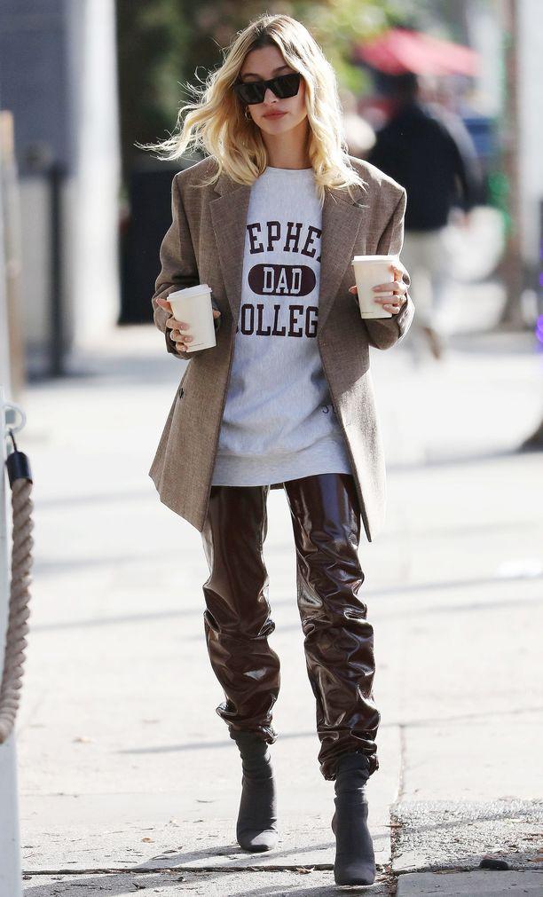 Hailey Bieberin kiiltäväpintaiset housut näyttävät upeilta pitkän bleiserin ja rennon t-paidan kanssa.