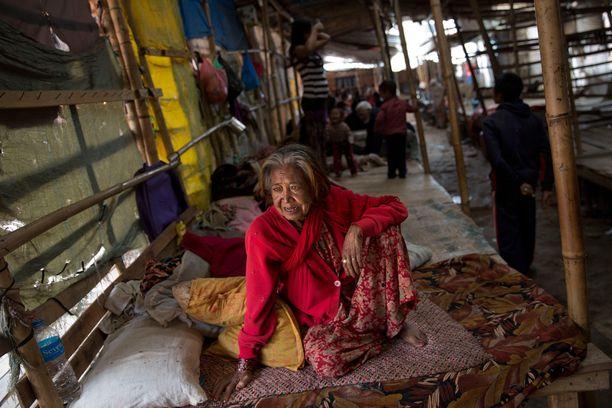 Iäkäs nainen oli päässyt katettuun suojaan Bhaktapurissa. Monet kotinsa menettäneet tai sen sortumista pelkäävät nukkuvat taivasalla tai teltoissa.