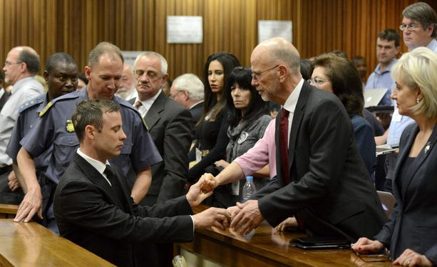 Oscar Pistorius piti setäänsä Arnold Pistoriusta kädestä ennen kuin poistui oikeussalista.