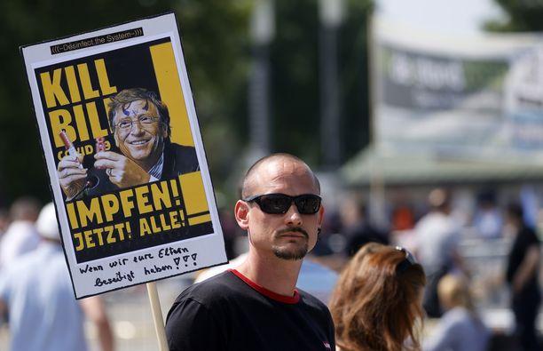 """Mies kantoi lauantaina Stuttgartissa kylttiä, jossa lukee """"rokottakaa nyt kaikki"""" sekä salaliittoteoreetikkojen kohde, Microsoftin perustaja Bill Gates."""