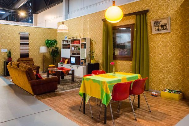 Värikkäät muovituolit ja pöytäliinat piristävät 70-luvun olohuonetta.