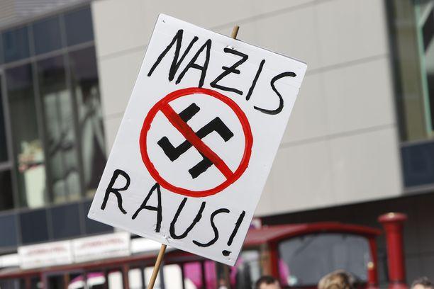 """Mielenosoittaja kantoi syyskuussa Saksan Mainzissa kylttiä, jossa luki """"Natsit ulos""""."""
