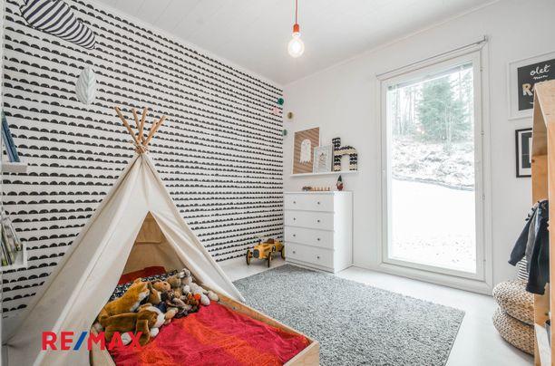 Vaalea tyyli jatkuu lastenhuoneessa. Valoa tarjoaa lattiasta kattoon ulottuva ikkuna. Lapsen sänky on laitettu hauskasti teltan sisään.