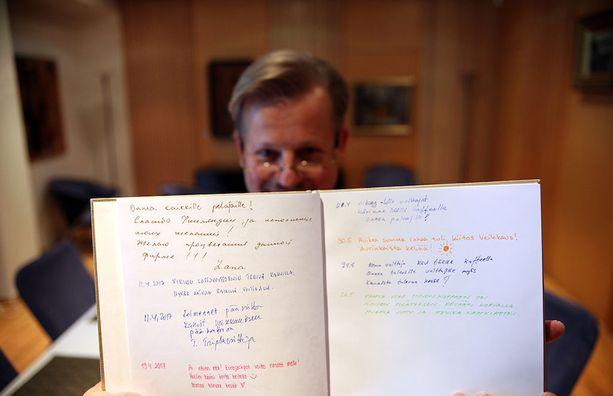 Tiedottaja Tero Talaslahti esittele Veikkauksen vieraskirjaa, johon suuren summan voittaneet halutessaan kirjoittavat terveisensä. Kuva on Veikkauksen kabinetista Vantaan Pähkinärinteestä.