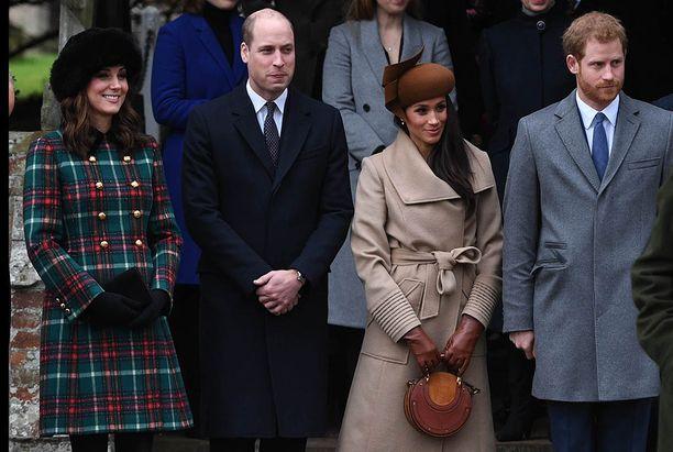 Vasemmalla herttuatar Catherine vierellään prinssi William. Oikeassa reunassa prinssi Harry vasemmalla puolellaan herttuatar Meghan.