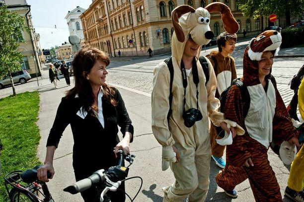 Vihreiden eduskuntaryhmän puheenjohtaja Outi Alanko-Kahiluoto katsoo, että eduskunnan pitkät istuntotauot kostautuvat istuntokuukausina, jolloin päivät venyvät ja päätöksenteon laatu heikkenee kansanedustajien väsymisen vuoksi. Kuvassa polttariporukka ohittaa Säätytalolle matkalla olevan Alanko-Kahiluodon.