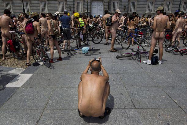 Mies otti valokuvan muista alastomista pyöräilijöistä. Hetkeä myöhemmin joukko ajoi läpi Madridin keskustan.