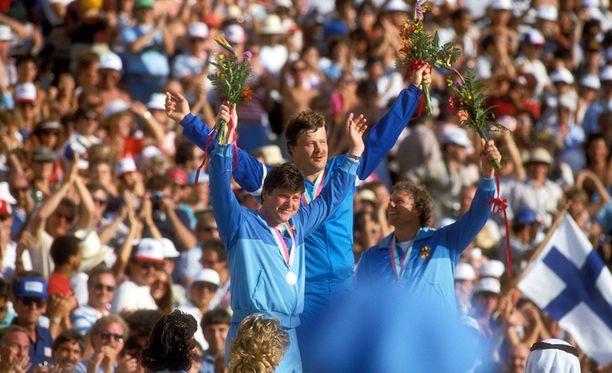 Juha Tiainen nousi Los Angelesissa 1984 korkeimmalle korokkeelle. Muut mitalistit olivat länsisaksalaisia. Olympiahopeaa heitti Karl-Hans Riehm (vas.) ja -pronssia Klaus Ploghaus.