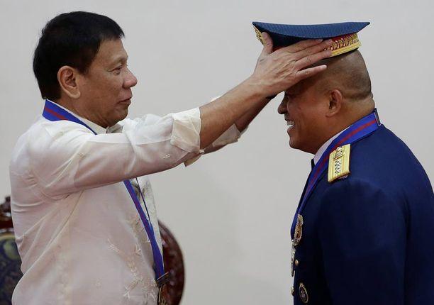Presidentti Rodrigo Duterte laittoi hatun uuden poliisiylijohtajan Ronald Dela Rosan päähän seremoniassa viime viikolla. Poliisilla on nyt lupa tappaa huumerikollisia.