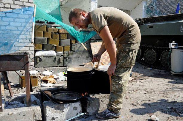 Sotilaat ovat yhdessä kohteessa jopa viikkoja. Keittiövuorossa syntyi torstaina soppaa. Taustalla neuvostoaikainen pesukone toiminnassa.