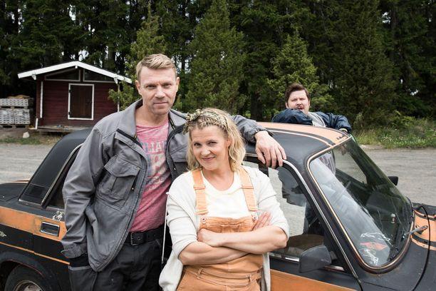 Näyttelijät Esa Latva-Äijö, Karoliina Vanne ja Janne Kataja poseeraavat Jaskan ladan kanssa.