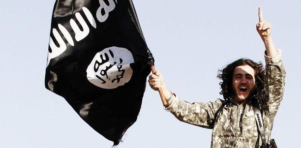 Isis-järjestön edustaja heiluttaa riemuiten lippua syyrialaisessa Raqqan kaupungissa 2014.