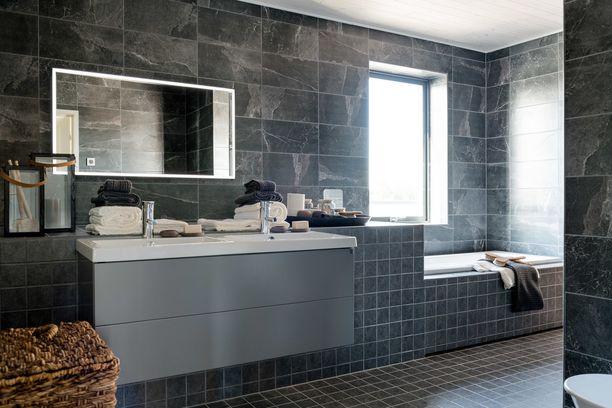 Mustanharmaa kylpyhuone on nyt trendikäs. Minimalistiseen ja suorakulmaiseen tyyliin yhdistettynä vaikutelma on tyylikäs ja dynaaminen.