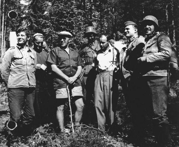 Edvin Laine keppi kädessä ohjaamassa Tuntemattoman sotilaan ensimmäistä elokuvaversiota. Väinö Linna (kolmas oikealta) on saapunut seuraamaan kuvauksia. Linnan oikealla puolella Tauno Palo majuri Sarastien rooliasussa.