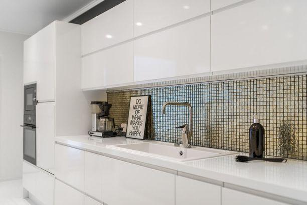 Laatan ei tarvitse olla tylsä. Kultaisena hohtava laatta antaa tälle modernille ja valkoiselle keittiölle näyttävän ilmeen.