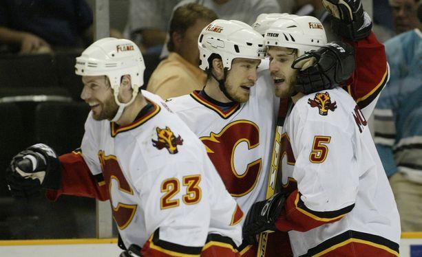 Calgary Flamesin Martin Gelinas ja Andrew Ference juhlivat Steve Montadorin (oikealla) kanssa hänen jatkoaikamaaliaan läntisen konferenssin ensimmäisessä finaalissa kaudella 2003-2004.