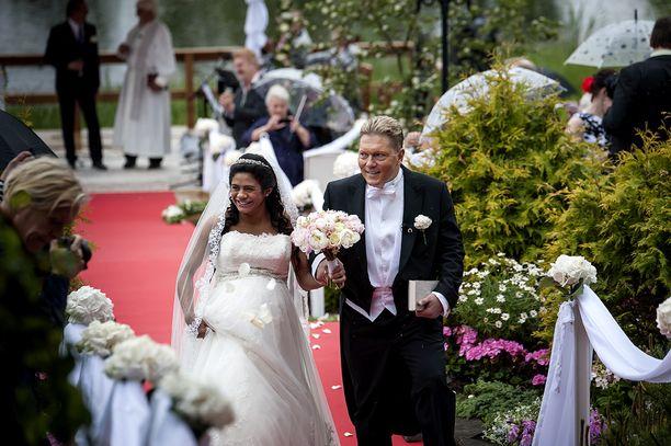Tuore aviopari hymyili leveästi kävellessään alttarilta vihkimisen jälkeen.