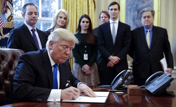 Kuvassa presidentti Trumpin Valkoisen talon lähipiiriä. Oikealla myös erotettu ex-neuvonantaja Steve Bannon.