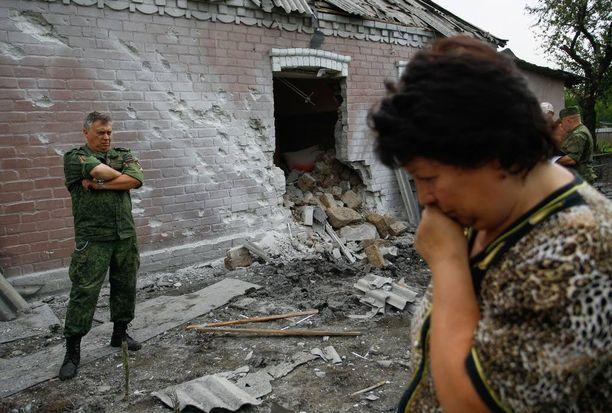 Nainen on järkyttynyt, ja Venäjän tukema separatisti seisoo tämän tuhoutuneen talon edustalla Donetskissa heinäkuussa.