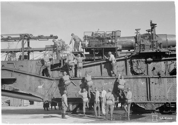 """Suomalaiset saivat """"Hangon-motin"""" purkauduttua saaliiksi muun muassa kuvassa olevan järeän 12-tuumaisen rautatietykin. Kuva on tykin koeammunnasta syyskuussa 1943; miehistö on komennettu tykille ja tykki laitetaan ampumakuntoon. Rautatietykit oli kuljetettu Suomen rataverkon kautta Neuvostoliiton tukikohtaan Hankoon syksyllä 1940."""