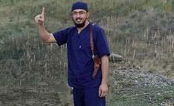 Issam Abuanza poseerasi Facebookissa lääkärinvaatteet päällään ja asekotelo olallaan.